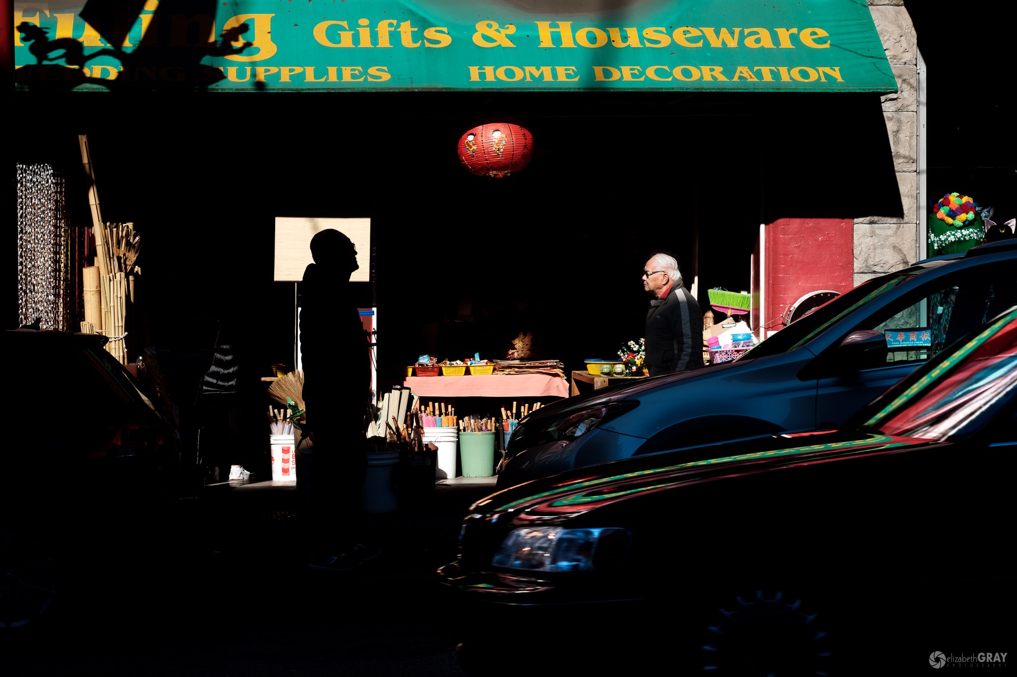 Gifts and Houseware - In my first attempts to capture this photo, the silhouetted figure was not centred within the bright sign. Luckily, he was waiting for someone and I could move slightly so that his entire head was silhouetted. I got lucky when a dark car drove past, adding reflections to the foreground.